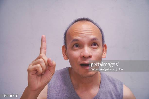 close-up of man gesturing while looking away against gray background - 人差し指 ストックフォトと画像
