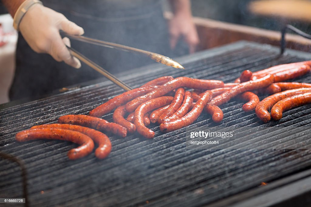 Close-up of man hand, cooking spicy browned sausages on : Stock Photo
