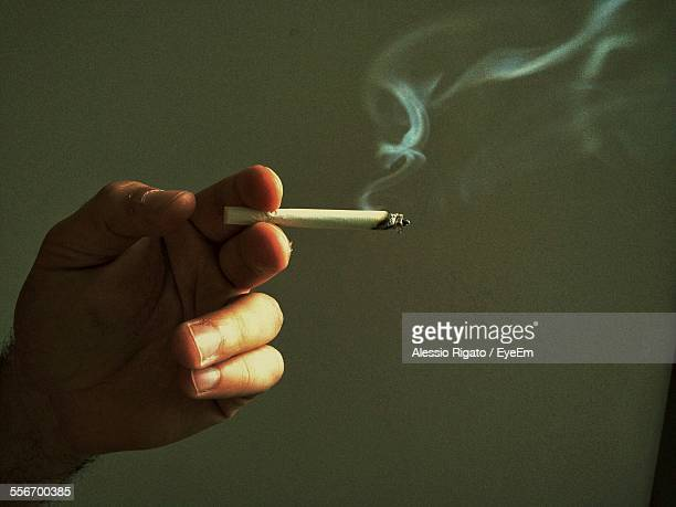 Close-Up Of Man Hand Holding Cigarette