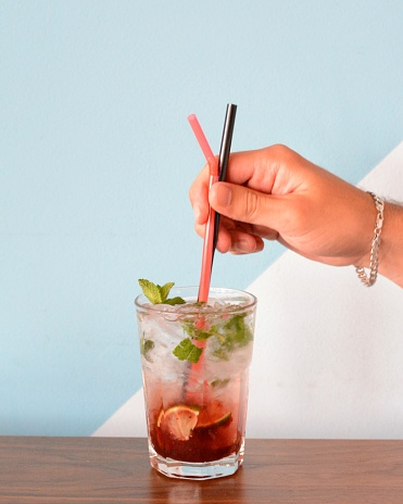Close-Up Of Man Hand Holding Drinking Straws In Cold Drink Against Wall - gettyimageskorea