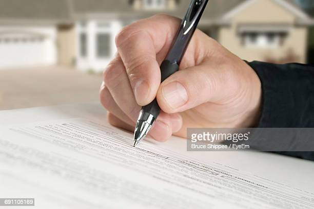 Close-Up Of Man Hand Holding Pen On Paper With Text