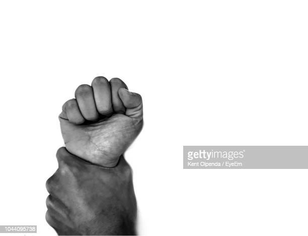 close-up of man hand holding woman fist against white background - violence stock pictures, royalty-free photos & images