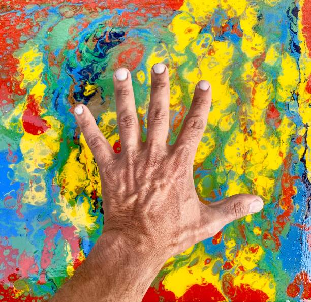 Close-Up Of Man Hand Over Colorful Table