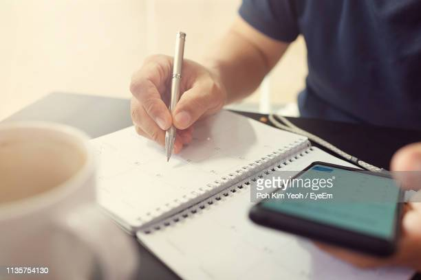 close-up of man hand using mobile phone while writing in calendar - calendar stock pictures, royalty-free photos & images