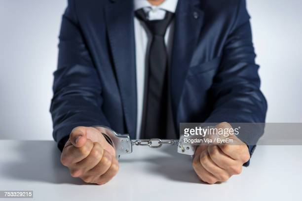 Close-Up Of Man Handcuffed Over White Background