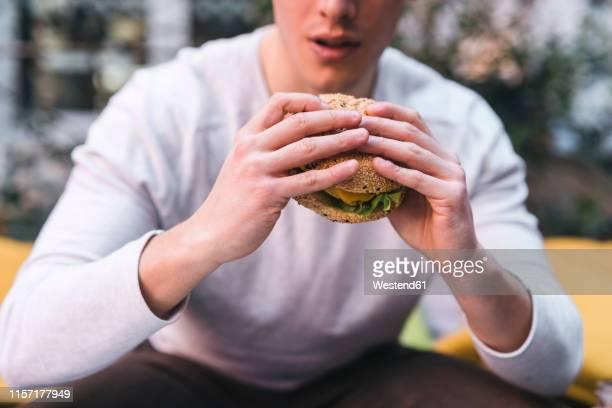 close-up of man having a vegan burger - veggie burgers stock pictures, royalty-free photos & images
