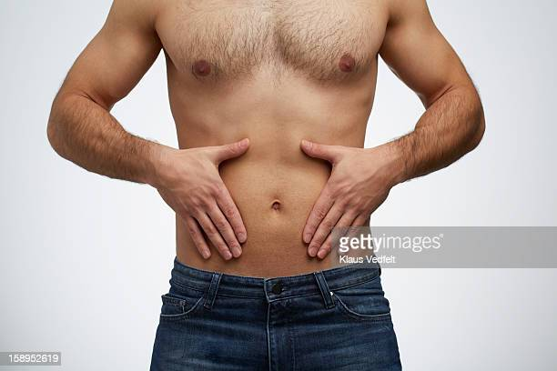 Close-up of man having stomach pain (front view)