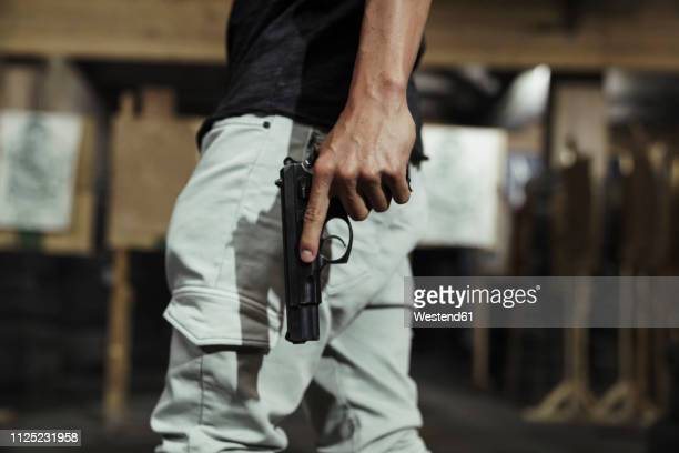 close-up of man holding a pistol in an indoor shooting range - 銃 ストックフォトと画像