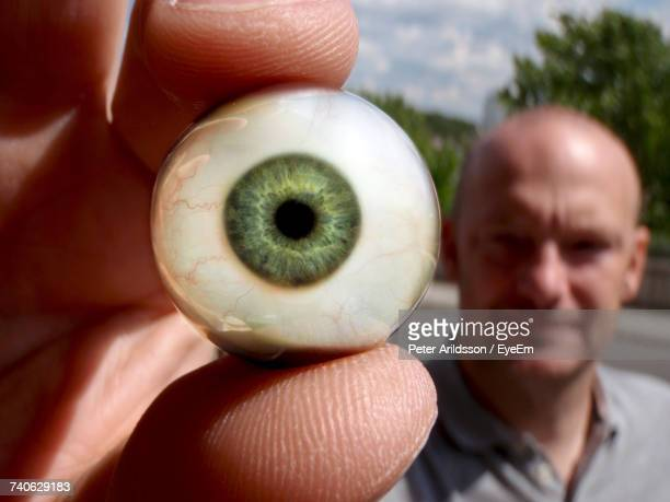 Close-Up Of Man Holding Artificial Eye