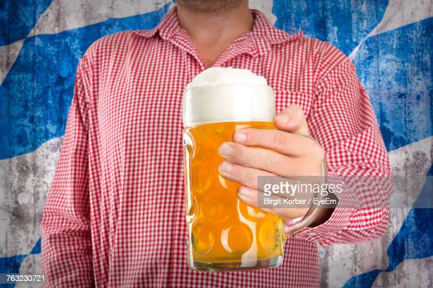 Close-Up Of Man Holding Beer Glass Against Wall