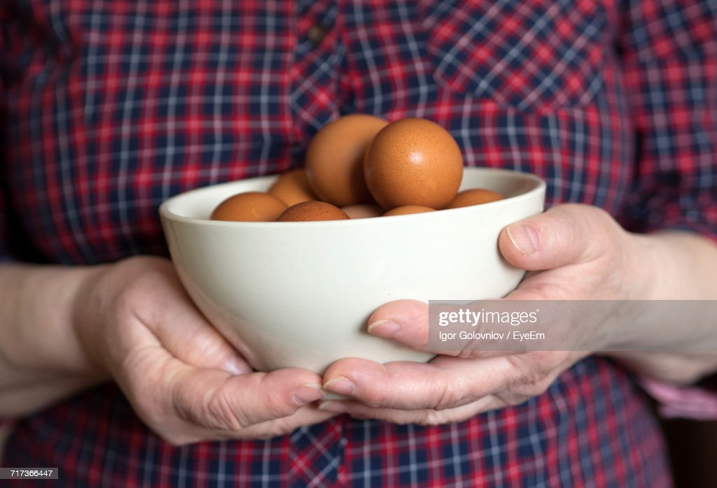 Close-Up Of Man Holding Bowl Of Egg : Stock Photo