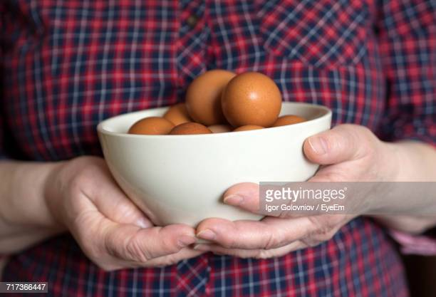close-up of man holding bowl of egg - igor golovniov stock pictures, royalty-free photos & images
