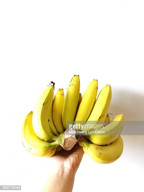 Close-Up Of Man Holding Bunch Of Banana On White Background