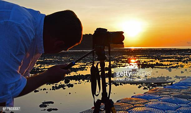 Close-Up Of Man Holding Camera At Pier By Sea During Sunrise