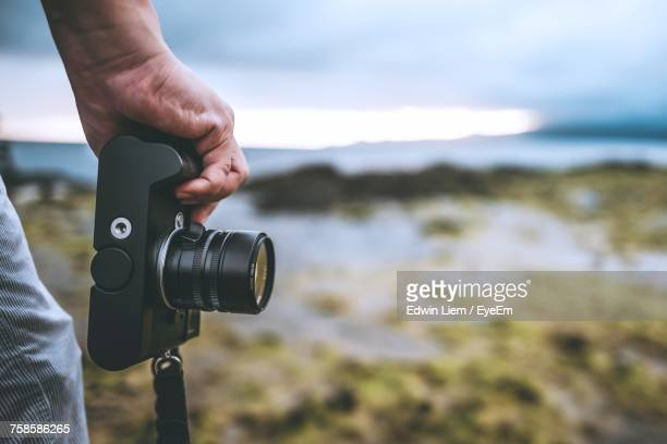 close-up of man holding camera - passion stock pictures, royalty-free photos & images
