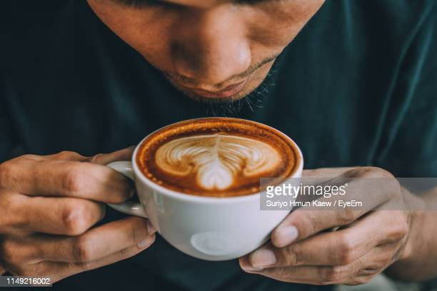 close-up of man holding coffee cup - coffee drink stock pictures, royalty-free photos & images