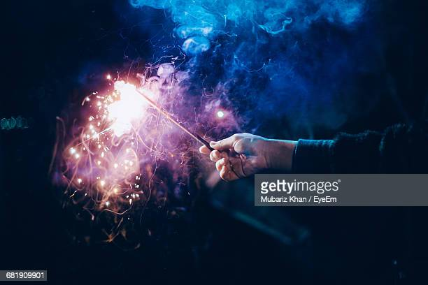 Close-Up Of Man Holding Firework At Night