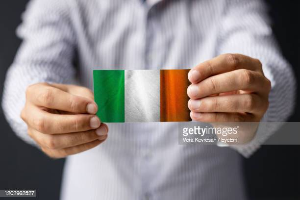 close-up of man holding irish flag. - diplomacy stock pictures, royalty-free photos & images