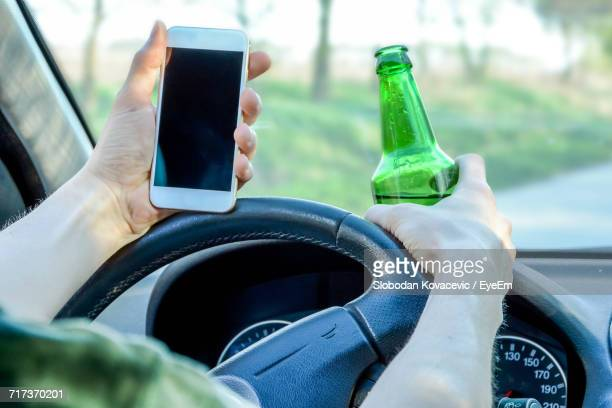 close-up of man holding mobile phone and beer bottle while driving - ubriaco foto e immagini stock