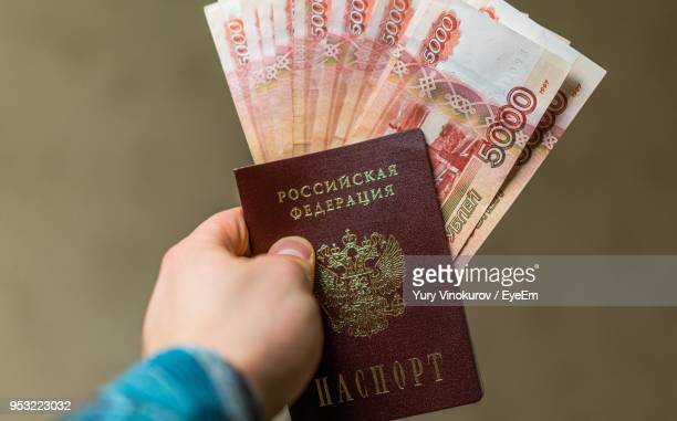 Close-Up Of Man Holding Money And Passport Against Brown Background