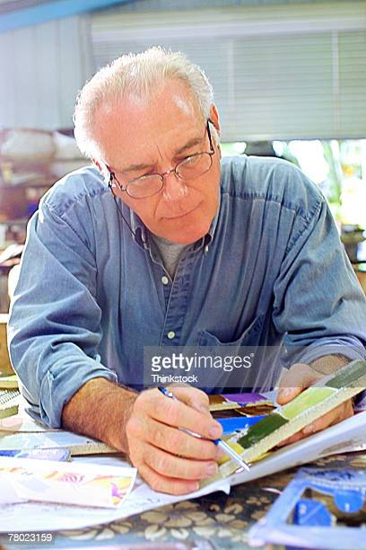 close-up of man holding paint sample and pen as he leans on table in his office studio. - illustrator stock photos and pictures
