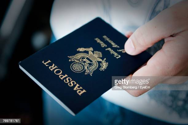 close-up of man holding passport - passeport photos et images de collection