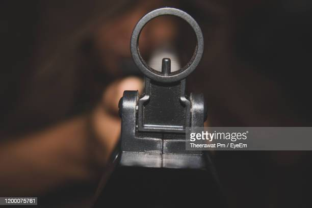 close-up of man holding rifle - rifle stock pictures, royalty-free photos & images