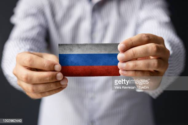 close-up of man holding russian flag. - patriotism stock pictures, royalty-free photos & images