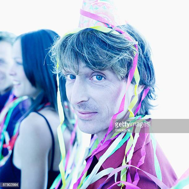 Close-up of man in a party cap covered in streamers