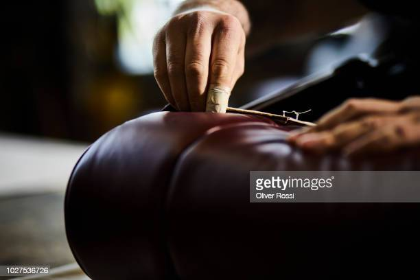 Close-up of man in an automobile upholstery workshop restoring seat