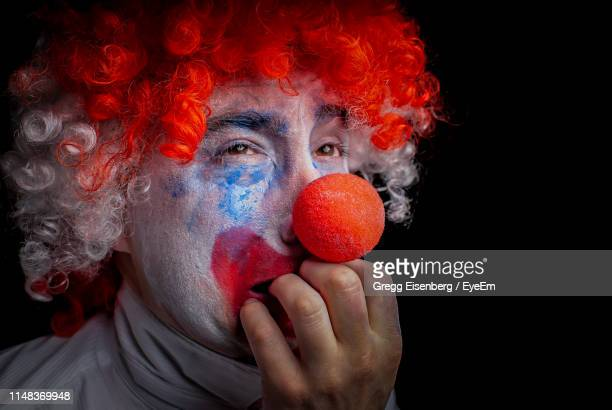 close-up of man in clown costume biting nails against black background - clown stock-fotos und bilder