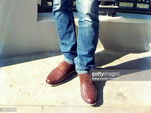 Close-Up Of Man In Jeans And Brown Leather Shoes