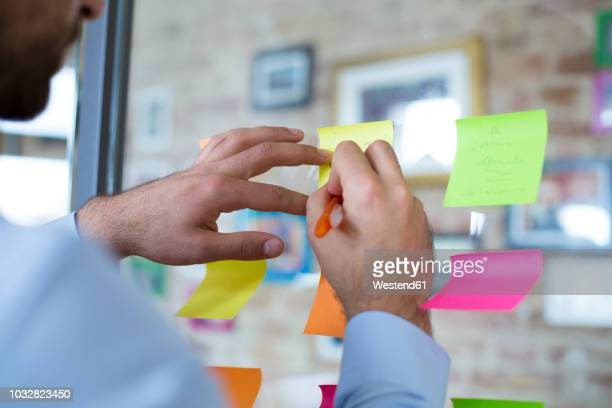close-up of man in office writing on adhesive note on glass wall - werkplaats stockfoto's en -beelden