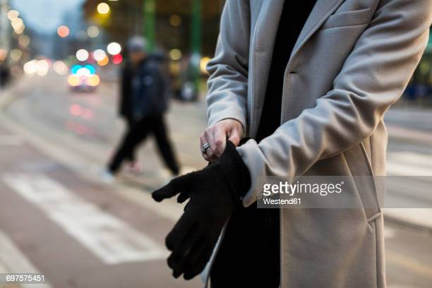 close-up of man in the city putting on gloves - coat stock pictures, royalty-free photos & images