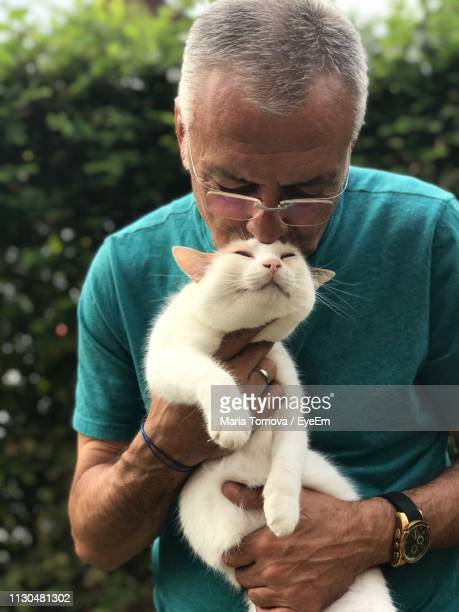 close-up of man kissing cat - pet -studio stock photos and pictures
