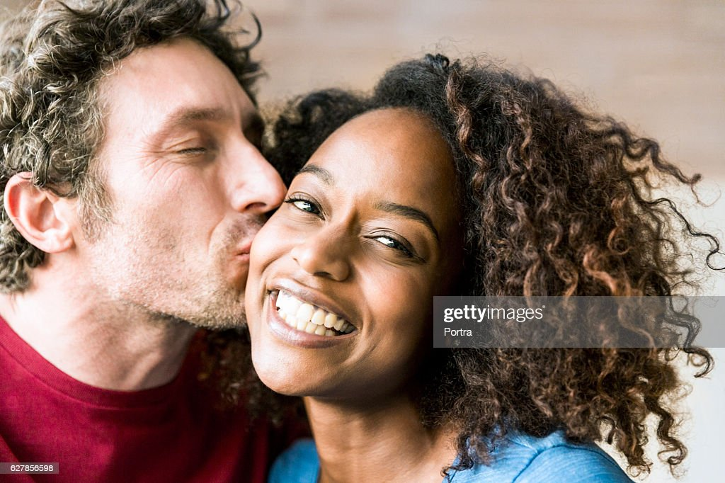 Close-up of man kissing cheerful woman on cheek : Stock Photo