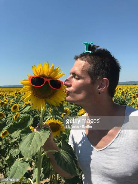 Close-Up Of Man Kissing Sunflower With Sunglasses At Farm