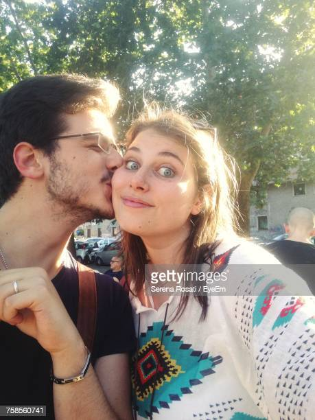close-up of man kissing woman at park - petite amie photos et images de collection