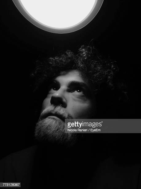 Close-Up Of Man Looking At Illuminated Lamp