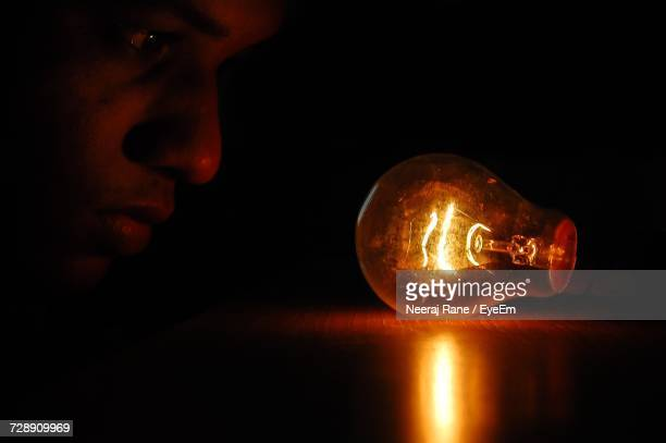 Close-Up Of Man Looking At Illuminated Light Bulb