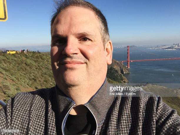 Close-Up Of Man Looking Away While Standing Against Golden Gate Bridge