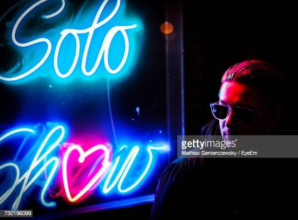 Close-Up Of Man Looking Away While Standing Against Illuminated Neon Lights