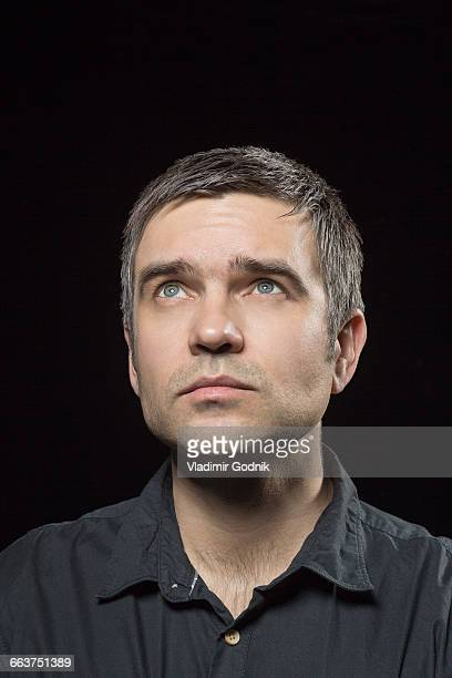 Close-up of man looking up against black background
