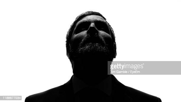 close-up of man looking up against white background - people stock pictures, royalty-free photos & images
