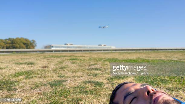 Close-Up Of Man Lying On Field Against Blue Sky