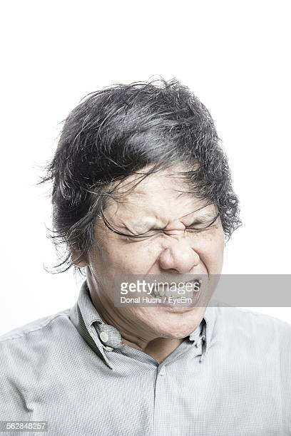 Close-Up Of Man Making Face Against White Background