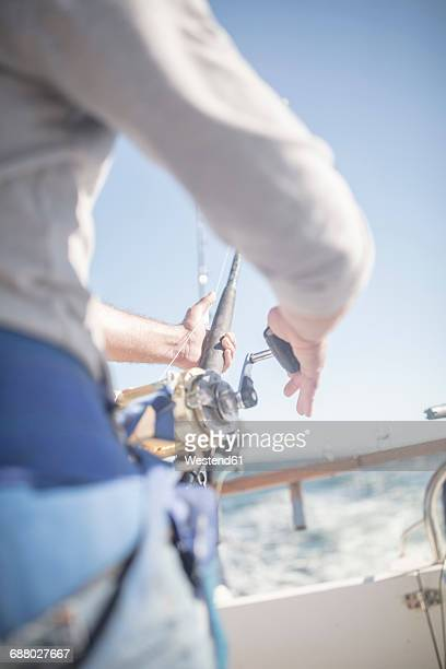 close-up of man on boat deep sea fishing - deep sea fishing stock photos and pictures