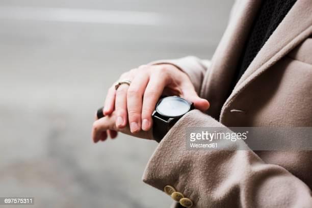 close-up of man outdoors checking the time - kleine uhr stock-fotos und bilder