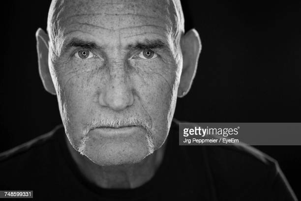 close-up of man over black background - black and white face stock photos and pictures