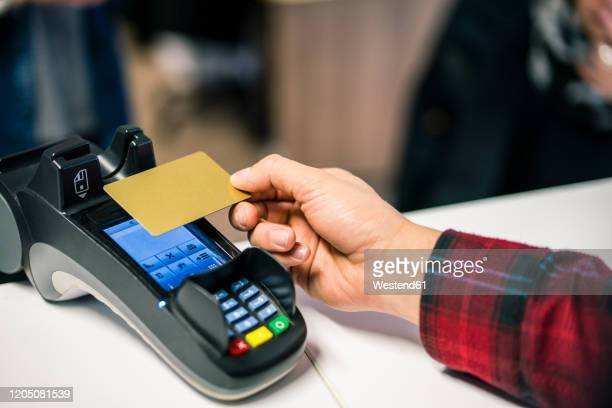 close-up of man paying contactless with credit card - contactless payment stock pictures, royalty-free photos & images